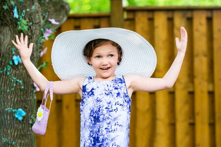 oversized: A young girl with a happy expression holds her arms out wearing a white oversized sun hat outside on a sunny spring day.