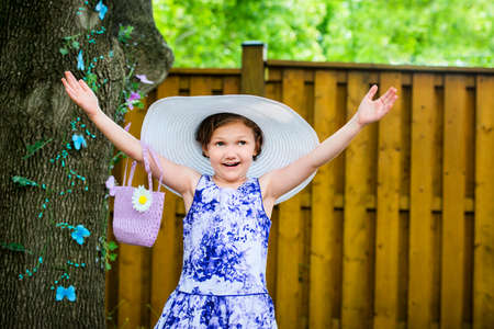 oversized: A young girl with a happy expression holds her hands up wearing a white oversized sun hat outside on a sunny spring day.