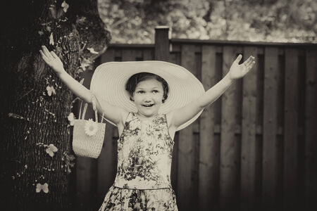 oversized: A young girl with a happy expression holds her hands up wearing a white oversized sun hat outside on a sunny spring day.  Filtered and toned for a retro, vintage look.