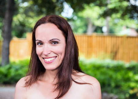 An attractive brunette woman in her 40s poses outside in a park like setting on a sunny day during the summer season.  Room for copy space. Stock Photo