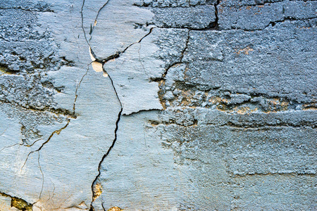 A close up view of an old cracked concrete wall painted in a light blue color.