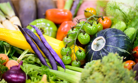 A close up of a variety of colorful organic vegetables at a farmers market. photo