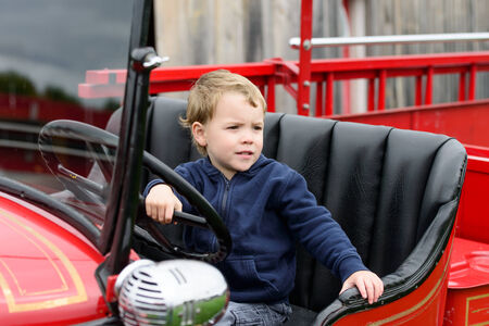 engine fire: A happy young boy sits in an old shiny vintage red fire truck holding on to the steering wheel looking out.