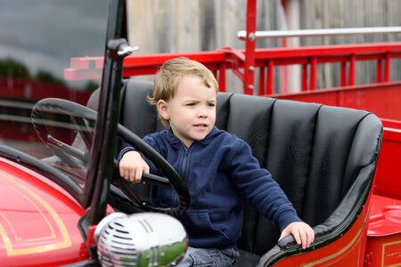 camion pompier: Un jeune gar�on heureux se trouve dans un ancien brillant mill�sime camion de pompiers rouge se tenant � la roue de direction regardant dehors.