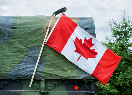 A close up of a Canadian flag attached to a hockey stick hanging on the side of a Canadian Armed Forces military personnel transport truck showing pride to honor Canadian national war heroes.