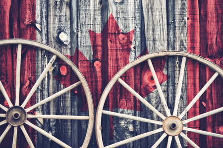 siding: A close up of two antique wagon wheels lying up against a building with wooden siding depicting the flag of Canada on its surface.  Filtered for a retro, vintage look.