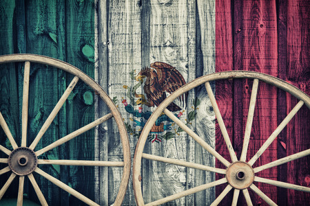 siding: A close up of two antique wagon wheels lying up against a building with wooden siding depicting the flag of Mexico on its surface.  Filtered for a retro, vintage look.