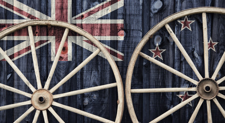 crux: A close up of two antique wagon wheels lying up against a building with wooden siding depicting the flag of New Zealand on its surface. Stock Photo
