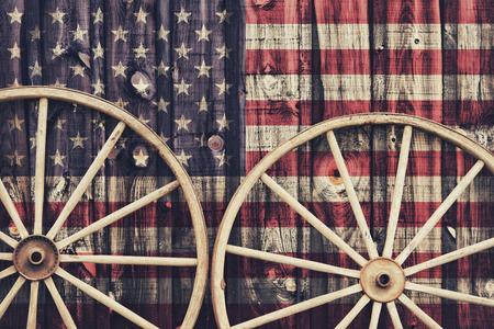 A close up of two antique wagon wheels lying up against a building with wooden siding depicting the flag of USA on its surface.  Filtered for a retro, vintage look.