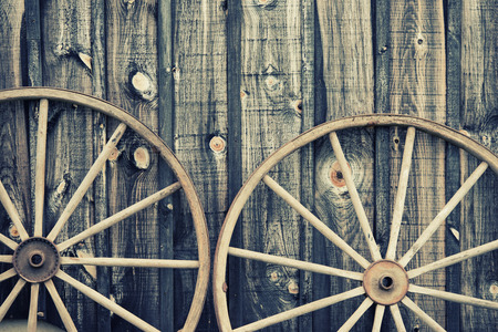 A close up of two vintage wagon wheels lying up against a building.  Filtered for a retro, vintage look. Imagens