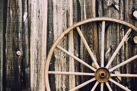 A close up of a vintage wagon wheel lying up against a building partially in the frame.  Filtered for a retro, vintage look.