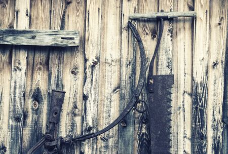 Old antique rusty logging tools hanging on the side of a wooden building.  Filtered for a retro, vintage look.