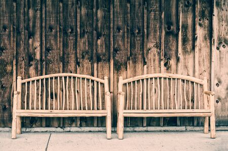 Two rustic wooden log benches sit side by side outdoor against a building wall made of wooden siding.  Filtered for a retro, vintage look.