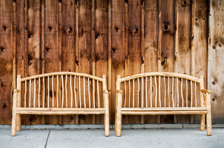 Two rustic wooden log benches sit side by side outdoor against a building wall made of wooden siding.