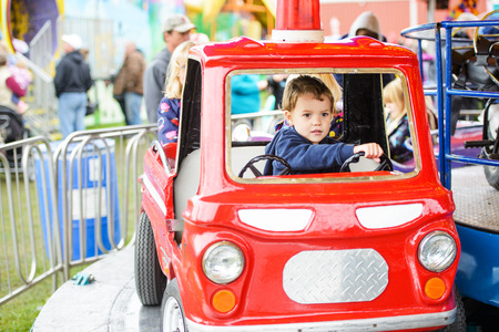 A happy young boy pretending to drive a firetruck on a merry-go-round at an amusement park. photo