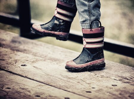 A close up view of a young boys feet wearing fireman rain boots.  The boots are dirty with mud.  Filtered to give retro, vintage look. Standard-Bild