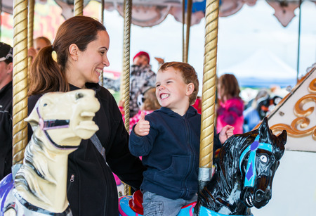 A happy mother and son are riding on a carousel together sharing a moment, smiling at one another having fun at an amusement park.  The boy holds a thumbs up at the mother. Stock Photo