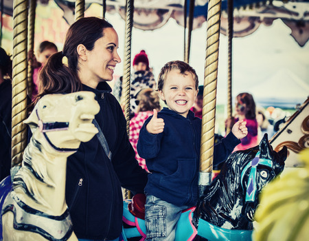 A happy mother and son are riding on a carousel together, smiling and having fun at an amusement park.  The boy holds a thumbs up.  Filtered for a retro, vintage look.
