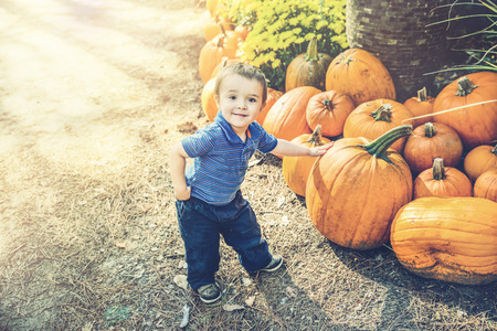 A young boy poses with his hand resting on a pumpkin he has picked at a farm during the autumn season.  Filtered for a retro, vintage look.