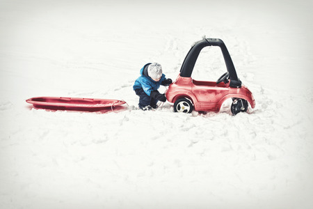 attaches: A young boy dressed for cold weather attaches a red sled with a rope to his toy car during the winter season.  Filtered for a retro, vintage look. Stock Photo