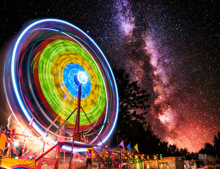 A ferris wheel taken at night under the stars using a long exposure to capture the circular motion of the lights.  Overlaid with the stars and milky way galaxy.