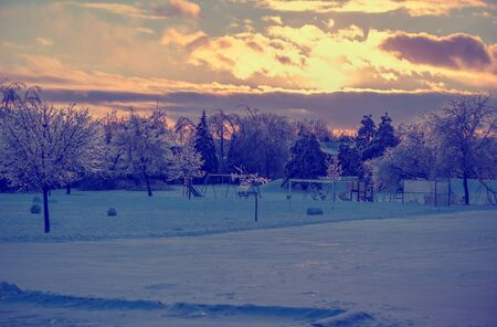 faded: The sun setting behind some clouds over a frozen park landscape with an icy playground in the distance after an ice storm.  The sunlight reflects off the ice on the tree branches making them shine.  Filtered for a retro, vintage look.