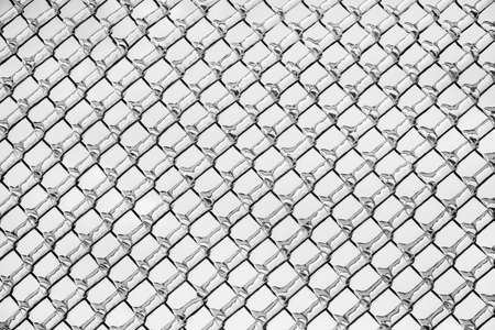 link up: A close up shot of thick layer of ice partially covering a frozen metal chain link fence after an ice storm. Processed in black and white.