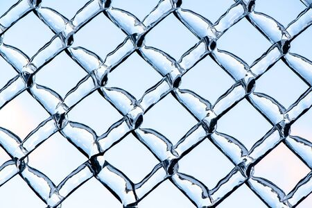 ice storm: A close up shot of thick layer of ice partially covering a frozen metal chain link fence after an ice storm.  The image in the background of soft clouds in a blue sky is refracted by the ice. Stock Photo