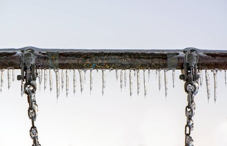 ice storm: A close up of the metal bar and chains hanging down of a swing at a playground covered in thick ice and icicles after an ice storm.