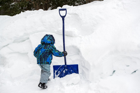 A young boy grabs a snow shovel beside a deep snowbank during the winter season.  Room for copy space.