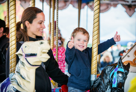 A happy mother and son are riding on a carousel together, smiling and having fun at an amusement park.  The boy holds two thumbs up. Stockfoto