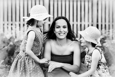 A family picture of a smiling mother together with her two happy daughters on either side of her.  Processed in black and white.