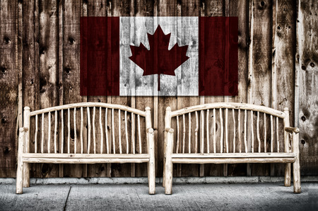 grunge layer: Two rustic wooden log benches sit side by side outdoor against a building wall made of wooden siding with a Canada flag hanging on the wall just above the benches.  A grunge layer is added to a Canada flag. Stock Photo