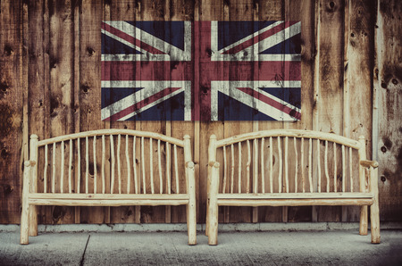 timber bench seat: Two rustic wooden log benches sit side by side outdoor against a building wall made of wooden siding with a United Kingdom flag hanging on the wall just above the benches.  A grunge layer is added to a United Kingdom flag. Stock Photo