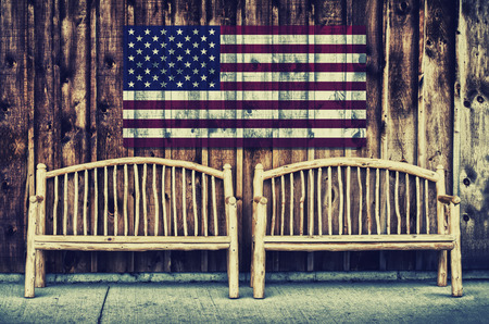 grunge layer: Two rustic wooden log benches sit side by side outdoor against a building wall made of wooden siding with a USA flag hanging on the wall just above the benches.  A grunge layer is added to a USA flag.  Filtered for a retro, vintage look.