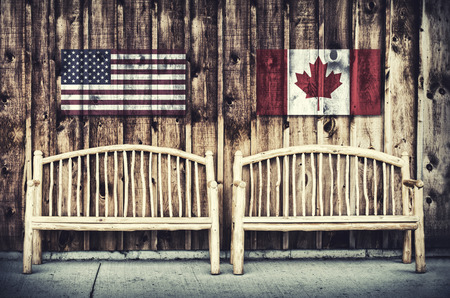 Two rustic wooden log benches sit side by side outdoor against a building wall made of wooden siding with a USA and Canada flag hanging on the wall just above the benches.  A grunge layer is added to a USA and Canada flag.  Filtered for a retro, vintage l
