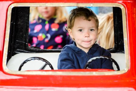 A close up of a happy young pensive boy sitting in a car on a merry-go-round at an amusement park. photo