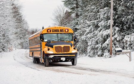 winter road: A school bus drives down a snow covered rural country road lined with snow covered trees after a snow storm during the winter season.  Series 3 of 3 Stock Photo