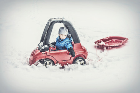 A young boy dressed for cold weather sits in a red toy car stuck in the snow pulling behind a red sled during the winter season.  Filtered for a retro, vintage look. Standard-Bild