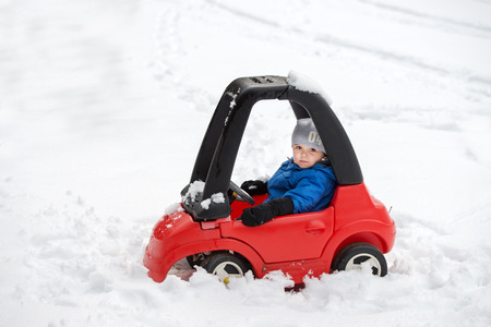A young boy dressed for cold weather sits in a red toy car stuck in the snow during the winter season. 스톡 콘텐츠