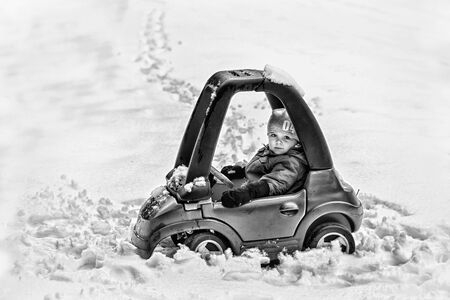 space weather tire: A young boy dressed for cold weather sits in a red toy car stuck in the snow during the winter season.  Processed in black and white.