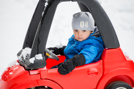driving conditions: A young boy dressed for cold weather with a serious expression sits in a red toy car stuck in the snow during the winter season.