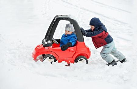 Um menino novo vestido para o tempo frio se senta em um carro vermelho do brinquedo preso na neve durante o inverno. Seu irmão mais velho ajuda, dando ao carro um empurrão por trás.