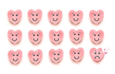 Three rows of pink heart shaped candy have happy faces.  The last candy on the bottom right corner has a sad expression with a bite taken out of it. photo