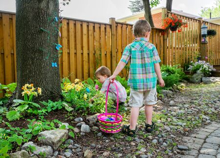 A boy stands holding a basket full of colorful Easter eggs while his little brother searches for more during an egg hunt outside in a beautiful garden.  Part of a series.