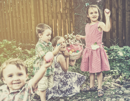 Two girls hold an Easter egg basket full of eggs; one of the girls holds up a pink Easter egg. A happy boy standing beside the girls looks down at a blue egg in his hands he has just found.  A little boy smiles looking at the camera holding up a pink egg  photo