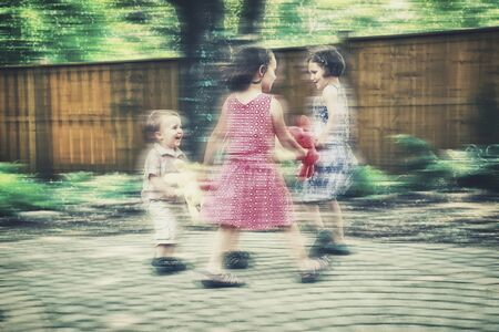 Girls and boys are holding hands together in a circle playing a game of ring around the rosie holding colorful plush bunny rabbits outside in a garden during an Easter party.  Intentional motion blur effect.  Part of a series.  Filtered for a retro, vinta Stock Photo