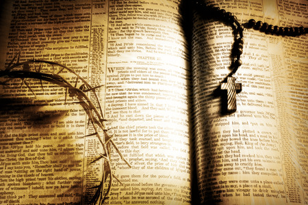 The Crown of Thorns and a wooden rosary casts dark shadows over an antique 19th century family bible open to St. Matthews recounting the cruxifiction of Christ. Filtered for an retro, vintage look.