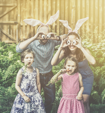 A funny family portrait on Easter of a mother and father wearing bunny ears and holding up silly eyes made from eggs as their children pose eating carrots outside in a garden during the spring season.  Filtered for a retro, vintage look.