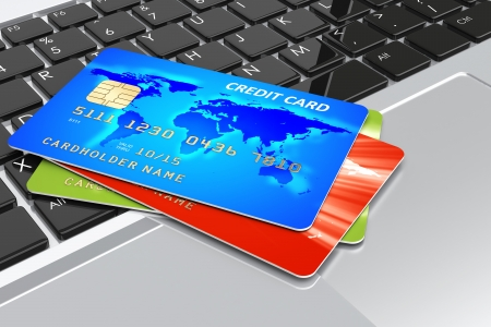 Credit cards on laptop keyboard. Internet shopping and e-commerce concept photo